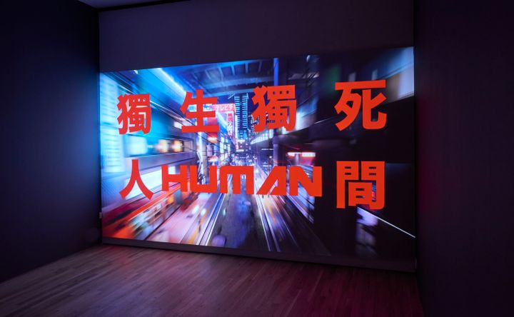 A large screen in a darkened gallery space features a futuristic scene, over which Chinese characters are written in red.