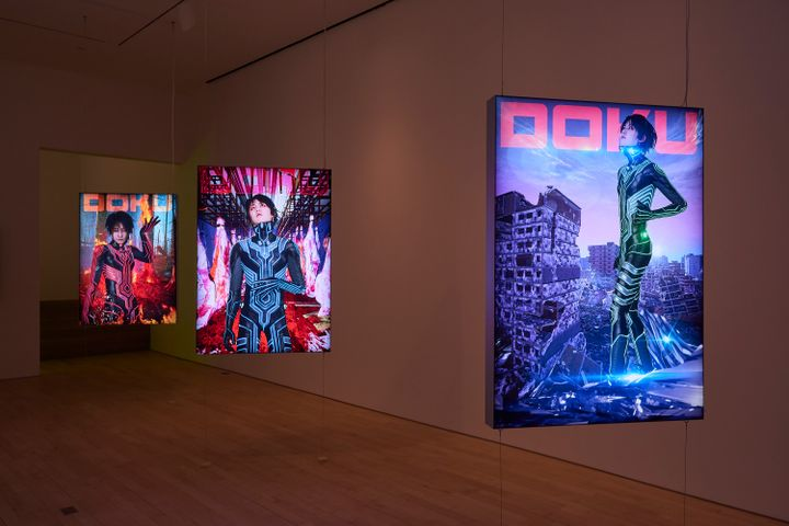 A series of three hanging screens in the gallery space show a figure in each in a futuristic landscape.