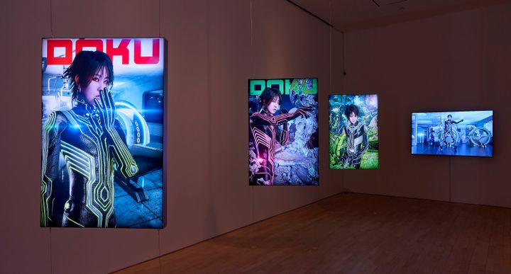 A series of four screens in the gallery space show a figure in each in a futuristic landscape.