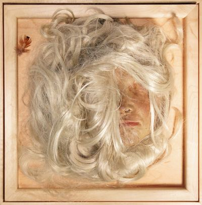 The face of a doll is concealed by a mass of white hair that surrounds it and sits within a frame.