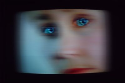 A blurry video shows a female face looking out at the viewer, their piercing blue eyes and pink lips remaining visible.
