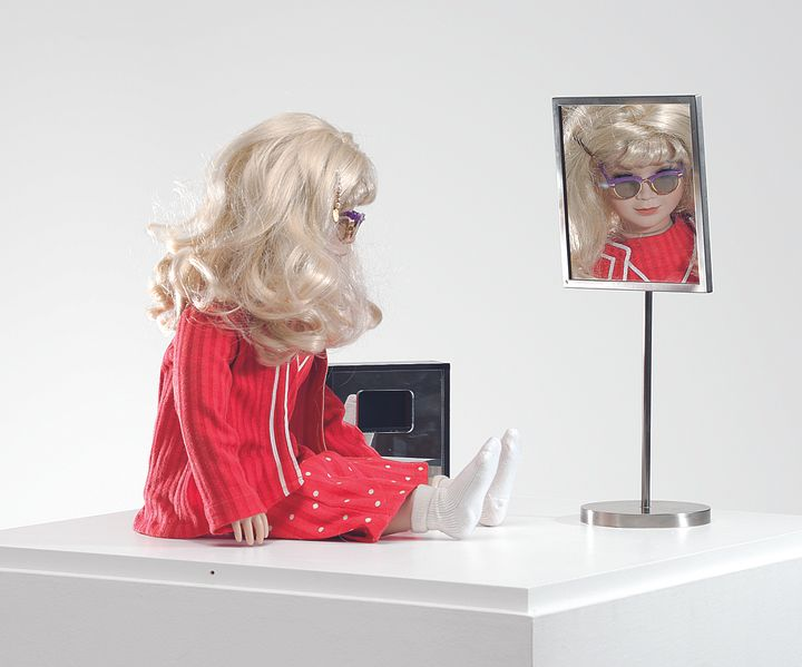 A doll with blonde hair and wearing sunglasses is dressed in a pink tracksuits and sits atop a white table top, in front of a small mirror.