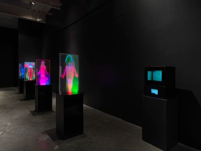 Four pedestals in the darkened exhibition space feature multicoloured projections of female figures in plexiglas.