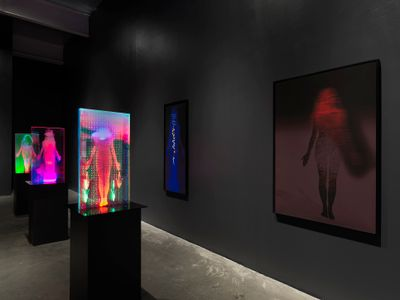 A series of three plexiglass sculptures within which colourful projections of women are shown, sit in a line in the darkened exhibition space, with another image of a female figure hung on the wall to the right.