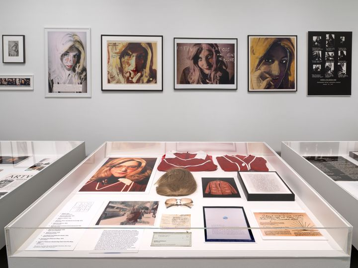 A line of black and white portraits of women overlaid with colour are situated behind a vitrine of archival imagery in the exhibition space.