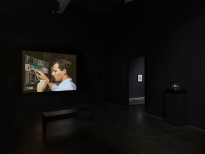 A male operator on the phone is captured in a film projection showing in a darkened exhibition space.