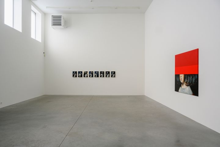 A white gallery space includes a series of small self-portraits of Mircea Suciu on the farthest wall, as well as a figure in Diego Velazquez's Las Meninas with the top half of their head concealed by a red bar of colour.