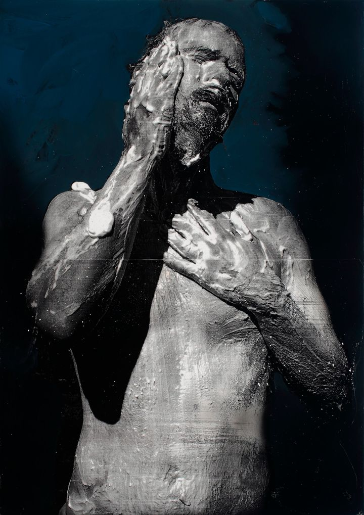 A painting of Mircea Suciu features the artist covering himself in foam, painted black and white against a blue-black background.