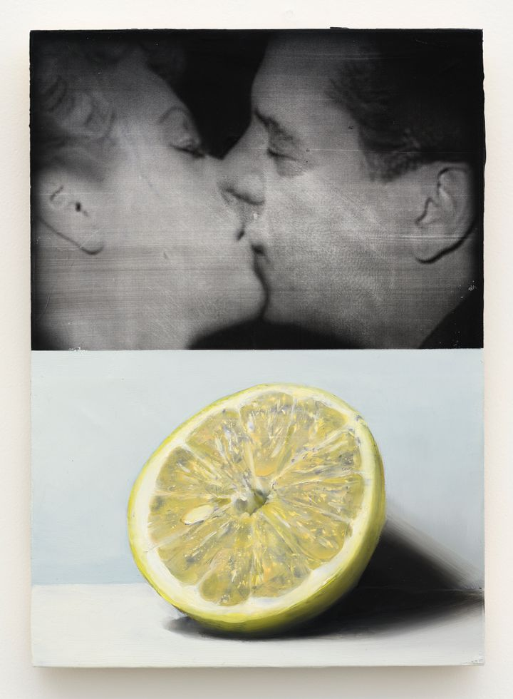 A realistic black-and-white painting resembling a fill still captures two people kissing at the top of a vertical canvas. At the bottom, half a lemon has been painted against a grey background.