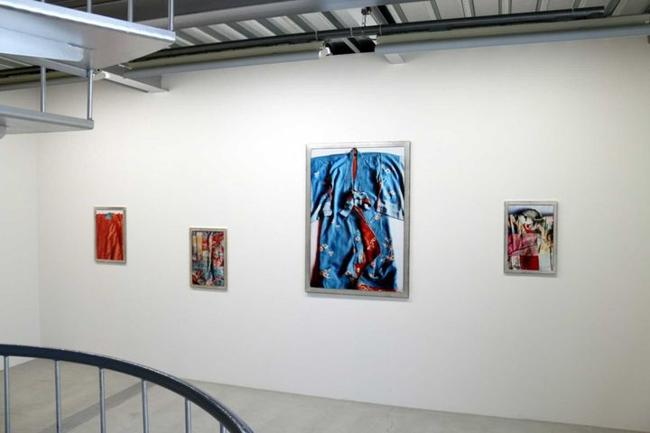 A series of closely cropped photos of brightly coloured kimonos are framed and hung along a wall in a white gallery space.