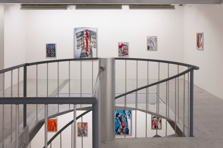 A photograph of a white gallery space captures a stairwell in the foreground, behind which the upper and lower floors are visible, and in them, a series of closely cropped photographs of brightly coloured kimonos that hang along the walls.