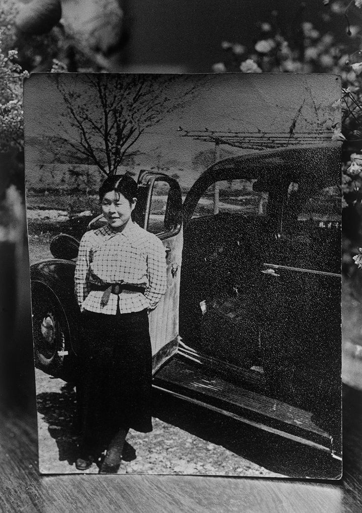 A black and white photograph of Miyako Ishiuchi's mother captures her standing in front of a vehicle, smiling at the camera.