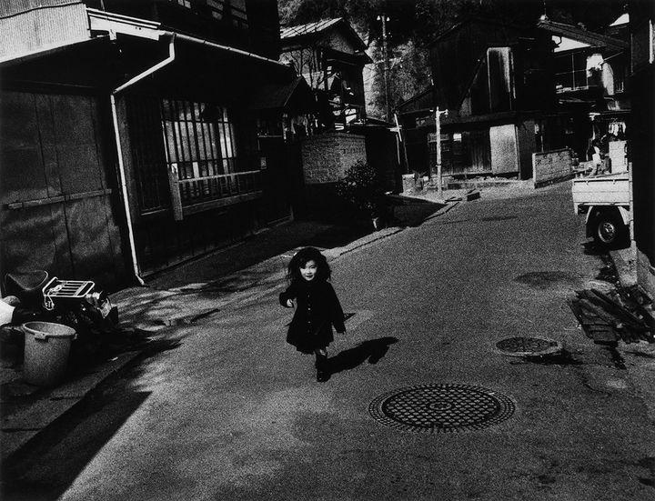 A black and white photograph by Miyako Ishiuchi captures a small child running through the street in Yokosuka, Kanagawa.