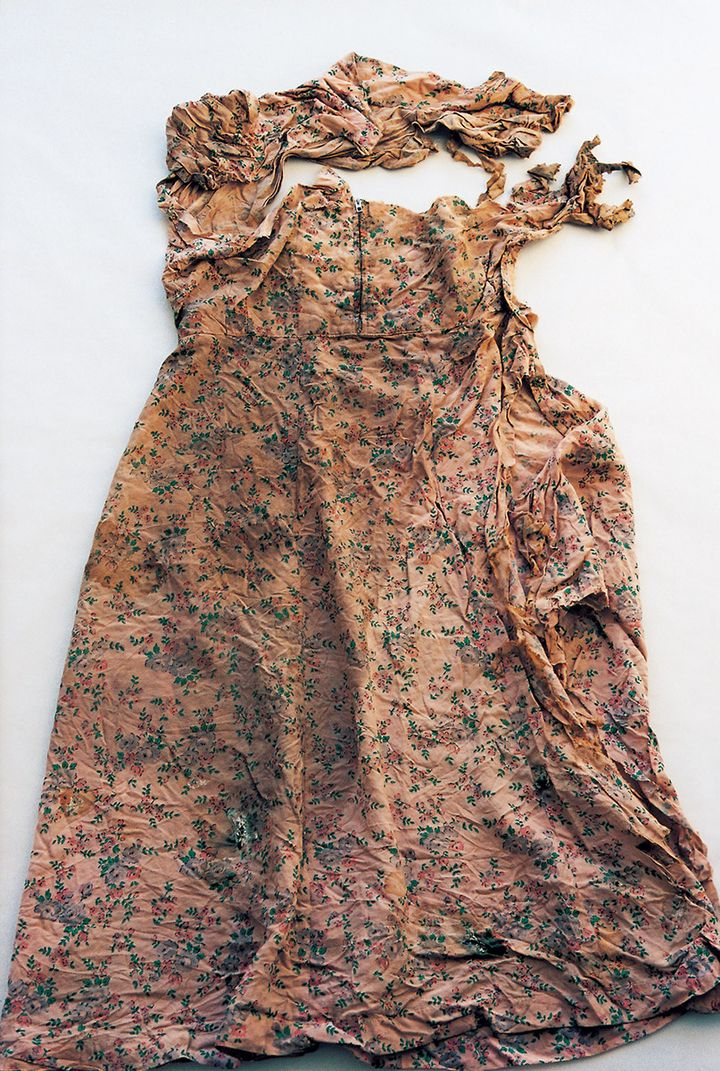 A crumpled, brown tinted floral dress is photographed against a white background.