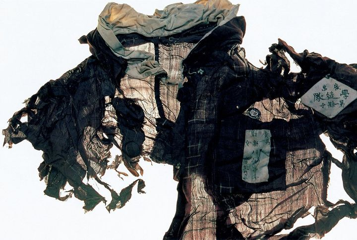 A torn blouse is photographed against a white background.