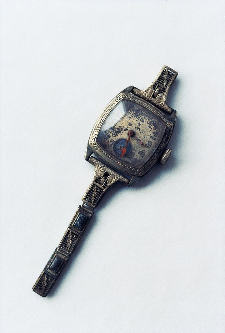 A damaged watch photographed by Miyako Ishiuchi up close against a white background.