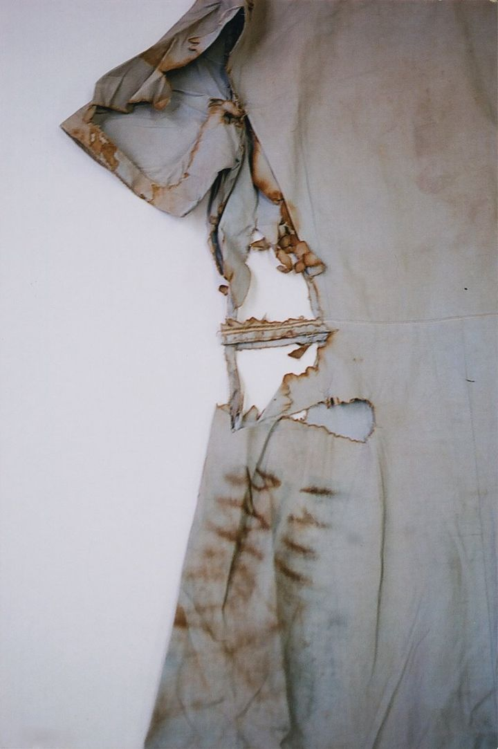 The left-hand side of a light blue blouse is photographed by Miyako Ishiuchi, highlighting holes and torn parts that run along its length.