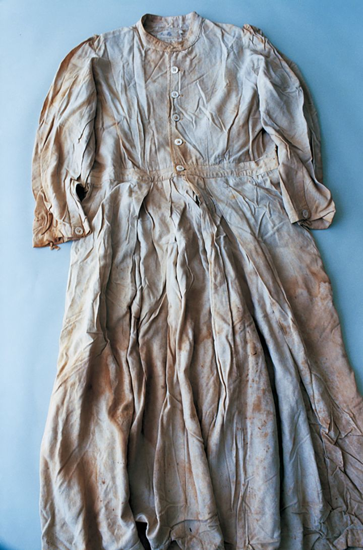 A brown tinted dress is photographed against a light blue background.