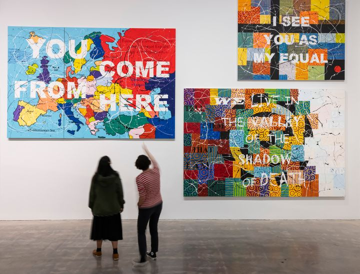 A group of four colourful paintings by Richard Bell in the gallery space with text in capital letters written across each of their surfaces, such as, 'I see you as my equal' and  'I come from here'