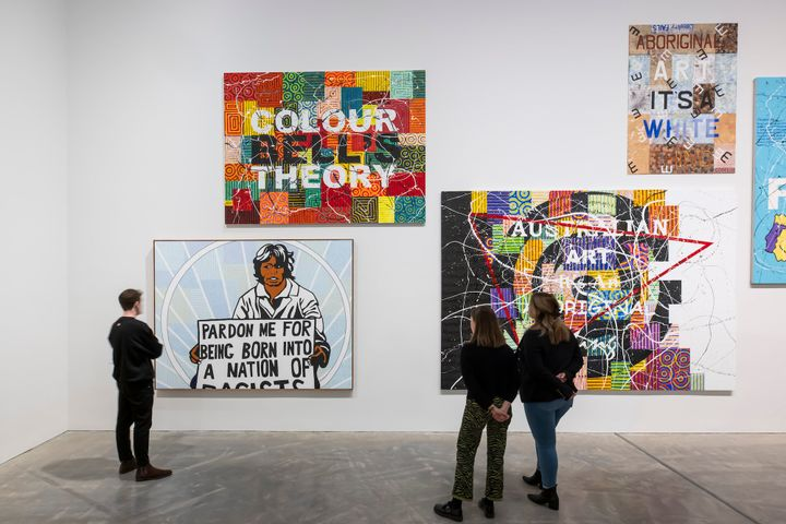 A group of four abstract paintings by Richard Bell in the gallery space with text in capital letters written across each of their surfaces, such as, 'Pardon me for being born into a nation of racists' and  'Bell's colour theory'