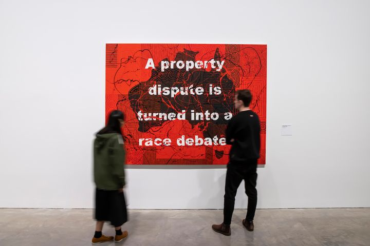 A painting of Australia by Richard Bell painted black against a red background, with the words 'A property dispute is turned into a race debate' written in capitals across the surface
