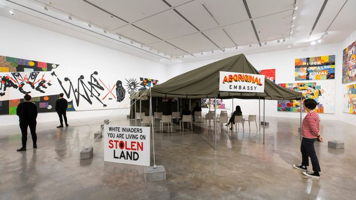 A series of paintings in the background of a gallery space is foregrounded by a tent titled 'Aboriginal Embassy',  in front of which a sign reads 'White Invaders You Are Living On Stolen Land'