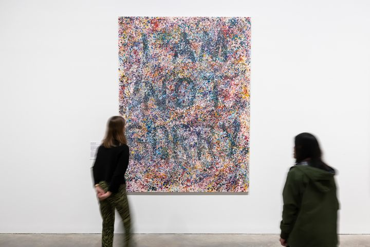 A speckled, abstract painting by Richard Bell in a gallery space that reads 'I am not sorry' across its surface