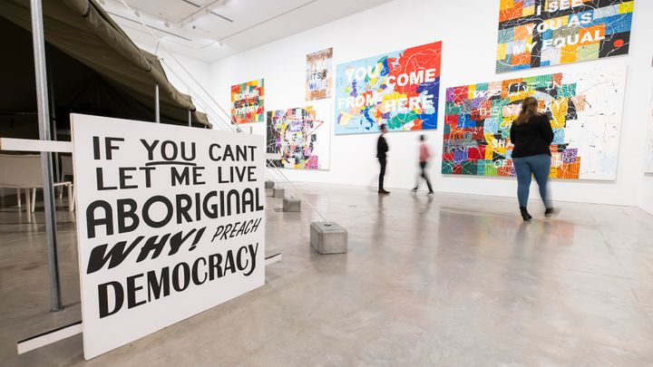 A series of paintings in the background of a gallery space is foregrounded by a sign that reads 'If you can't let me live Aboriginal, why preach democracy?'