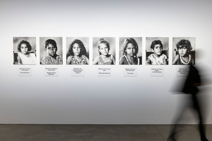 A series of seven black and white photographs of young children, forming an installation by Richard Bell in the gallery space