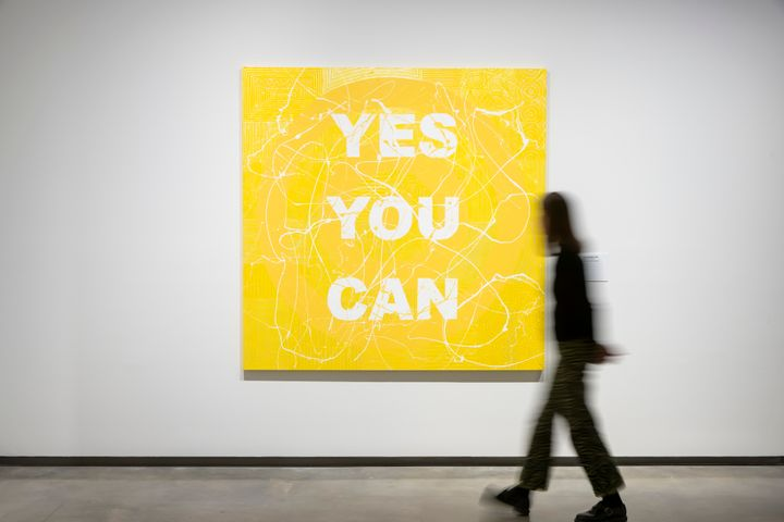 A yellow painting by Richard Bell in a gallery space, with the words 'Yes you can' written in white on the surface.