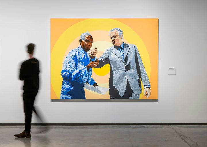A painting by Richard Bell in a gallery space of two men in suits against an orange and yellow background.