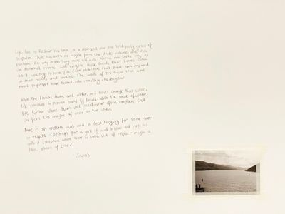 Paragraphs of hand-written text are visible on the white exhibition wall. Beneath this, a black and white photograph of a lake has been pasted.