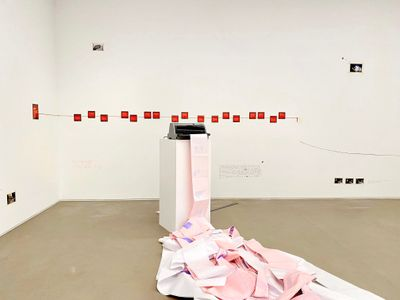 Pink paper spills from a dot matrix printer that is placed atop a long pedestal in a white gallery space.