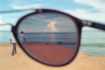 A photograph by Zainab captures a beach scene from behind the purple-tinted lens of a pair of sunglasses. A man can be seen walking on the beach in front of them.