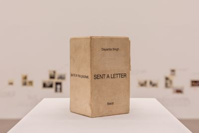 The cover of a book propped up upon a pedestal in the exhibition space reads 'Dayanita Singh: Sent a Letter'.