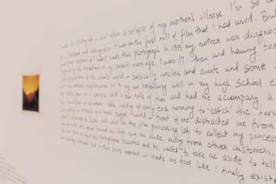 A wall in the exhibition space is photographed from an angle, capturing hand-written words across its surface.