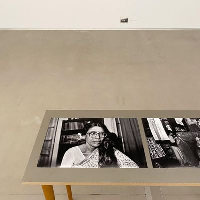 Black and white photographs are assembled on a long narrow table, including an image of a woman in glasses who appears to be talking to someone located just outside the frame.