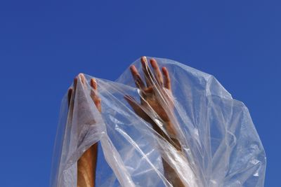 A photograph by Zainab captures a pair of hands reaching into the sky. The hands are covered by plastic sheeting, which is translucent against the blue sky.
