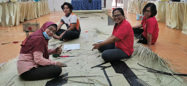 Three women and one male weaver work on a mat in the floor. In the forefront, a female weaver signals thumb's up to the camera.