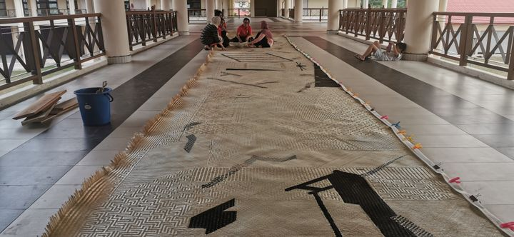 A large mat runs the length of an outdoor patio. In the distance, a group of weavers sit at the end of it.