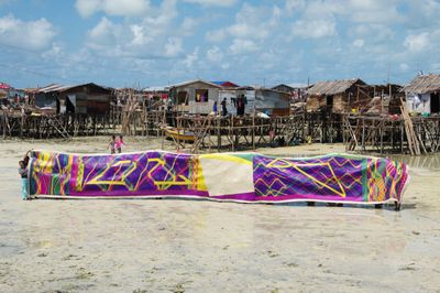 A group of people hold up a long, colourful, patterned woven mat in front of a cluster of houses on stilts. The tide of the ocean has gone out, so that they are standing on the sand.