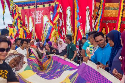 Semporna Lepa Regatta April 2019, the public escort Tikar-A-Gagah to the festival marina. It is crowded, and the mat runs through the crowd that is being held up by the public.