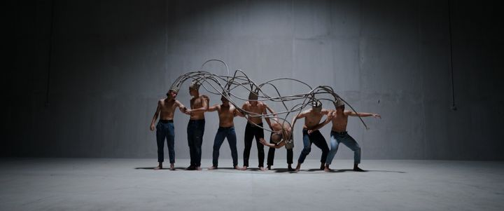 A still from Yee I-Lann's video PANGKIS (2021) features a septuplet of male dancers carrying a canopy of woven tubular cords, which are interconnected and sprawl out from individual hats.