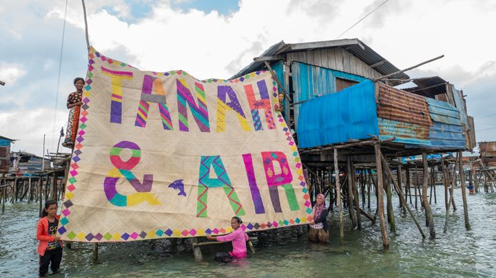 Two women stand in the water below a cluster of houses on stilts, and another woman stands on a platform above them. The three women hold up a large mat that reads 'Tanah & Air'. The writing is colourful and patterned with stripes and diamonds, and stands brightly against the beige background of the mat. There is a small dolphin between '&' and 'Air'.