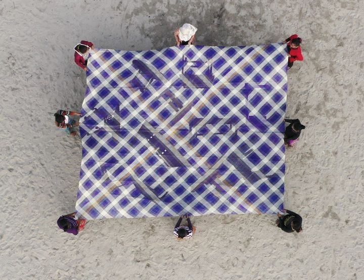 A purple and white criss-crossed mat featuring images of tables on its surface is held up by eight people standing on the sand. The supported mat is photographed from above.
