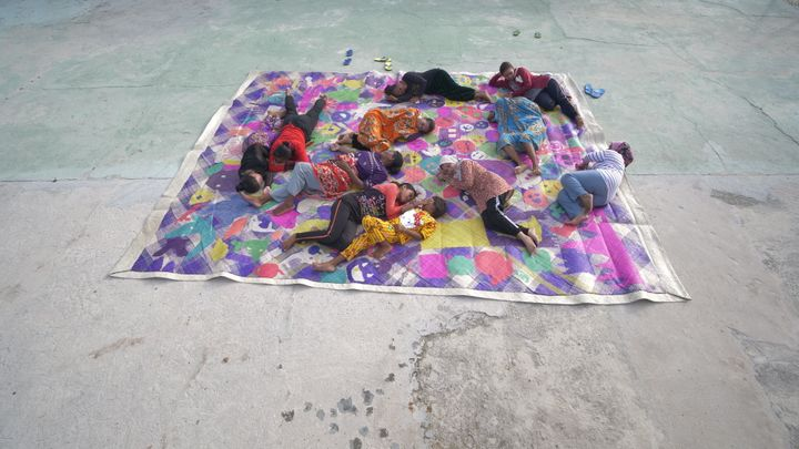 11 individuals, photographed from above, lie upon a colourful, woven mat on the floor.