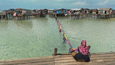 A long, narrow, colourful woven mat connects two wooden homes on stilts in the sea. Its length is supported by individuals holding it up.