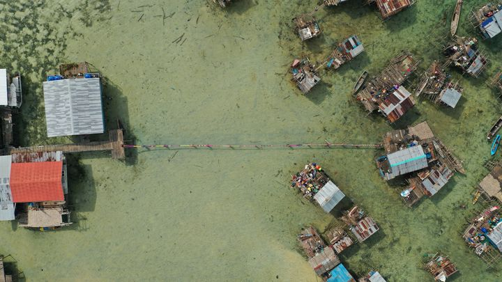 An aerial shot features the homes of a sea village, made up of houses on stilts. Two clusters of buildings are joined by a long narrow woven mat that has been unravelled by its carriers.