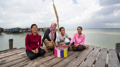 Four women sit on a raised wooden platform in the sea, smiling behind a rolled up segment of colourful woven mat that has been created by the artist Yee I-Lann and her collaborators. In the distance, there is a cluster of buildings on stilts in the water.