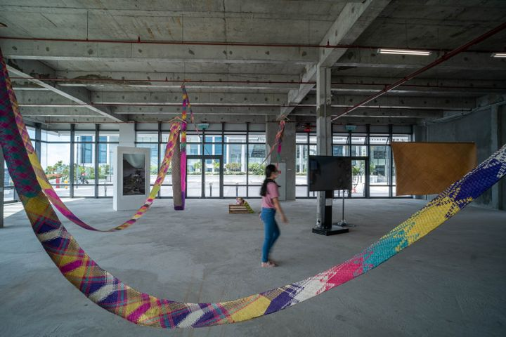 An industrial looking exhibition space with windows running along its far wall features a long woven mat that hangs throughout the space, with interlocking diamond patterns in different colours, including pink, green, yellow, and blue. A female audience member walks within it.